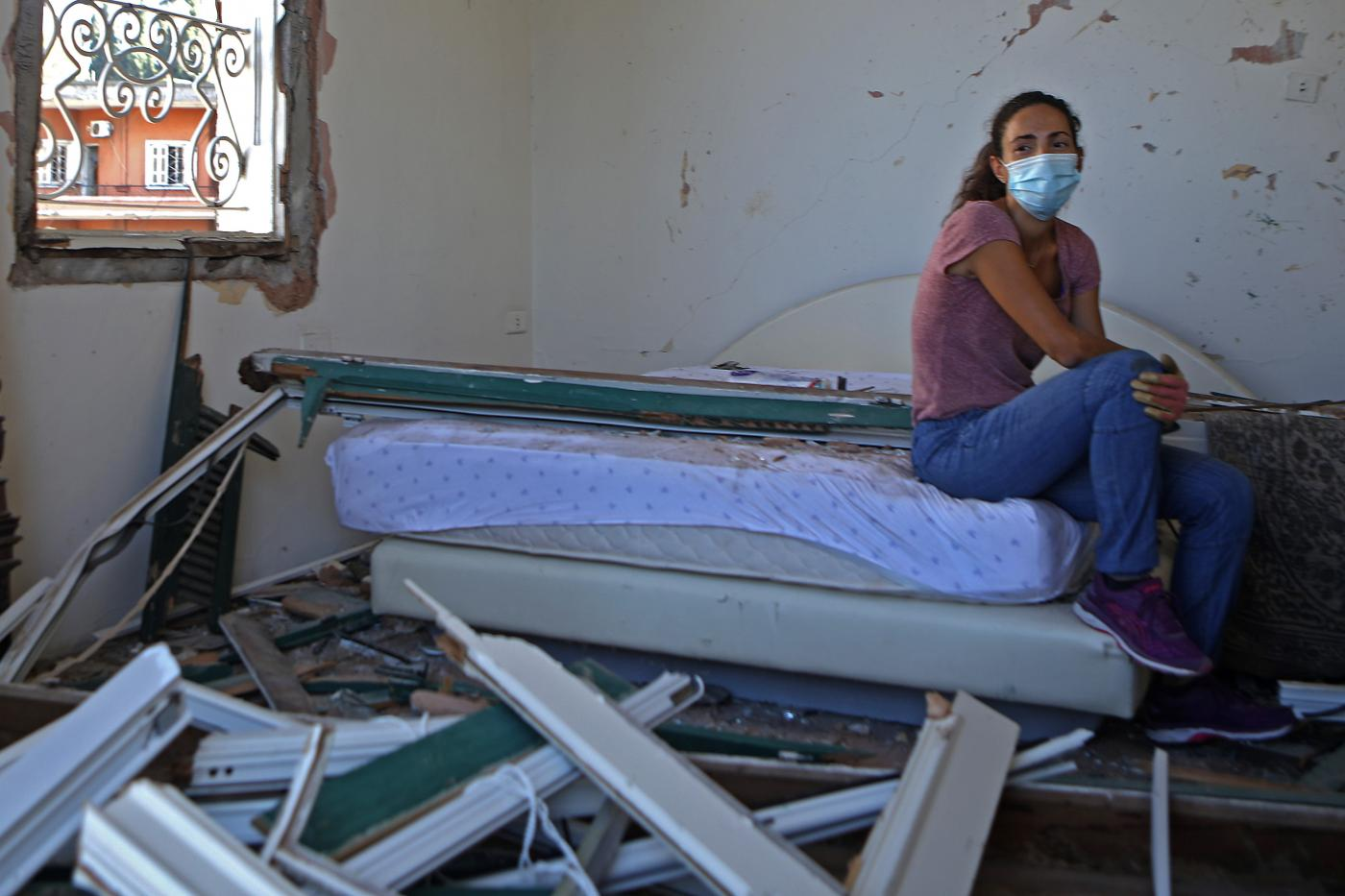 A Lebanese woman sits in her damaged bedroom in the damaged neighbourhood of Mar Mikhael in Beirut on 6 August (AFP)