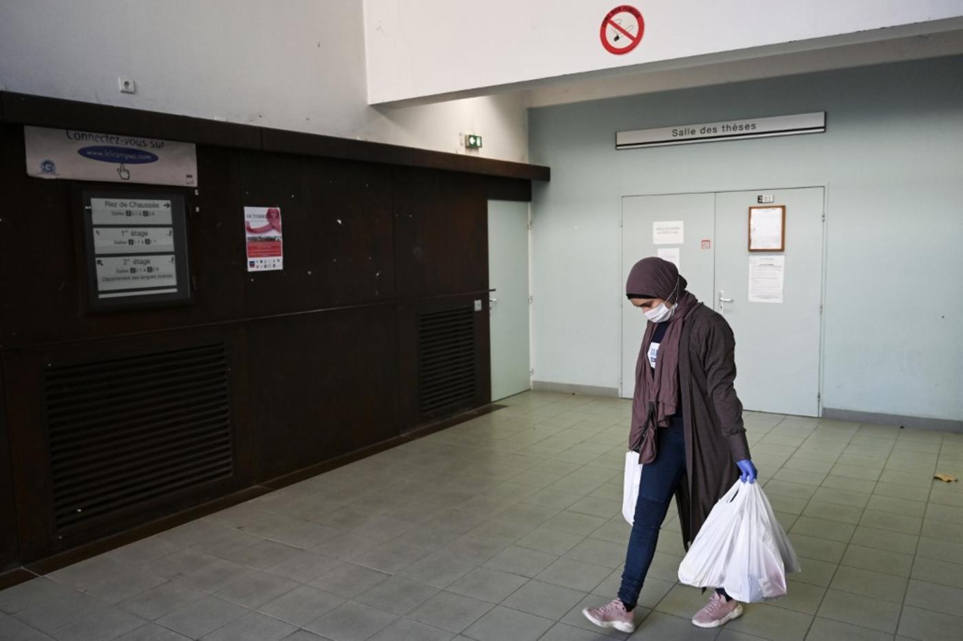 Une étudiante bénévole porte des sacs d'aide alimentaire sur un campus universitaire, le 17 novembre 2020 (AFP)