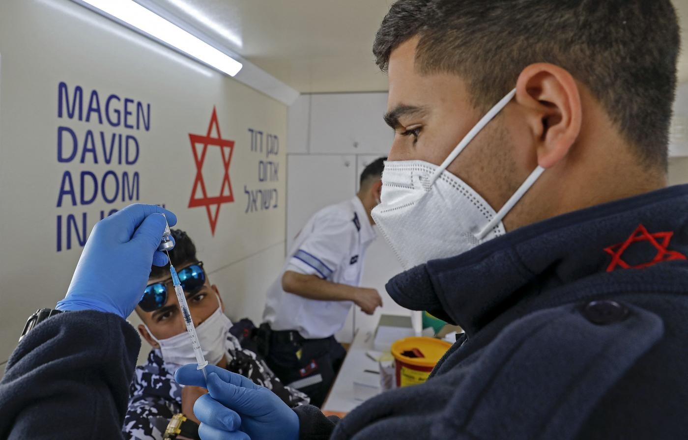 A paramedic with Israel's Magen David Adom medical services prepares a dose of the Pfizer-BioNTech COVID-19 vaccine to inoculate a Palestinian man in a mobile clinic on 26 February 2021, at the Damascus Gate in Jerusalem's Old City. (AHMAD GHARABLI / AFP)