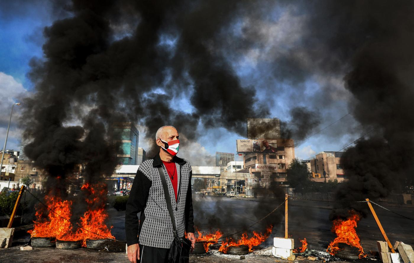 A man in mask a depicting the Lebanese flag stands next to flaming tires at a make-shift roadblock set-up by anti-government demonstrators in  Dora on the northern outskirts of Lebanon's capital Beirut on 8 March 8 2021 (Anwar Amro/AFP)