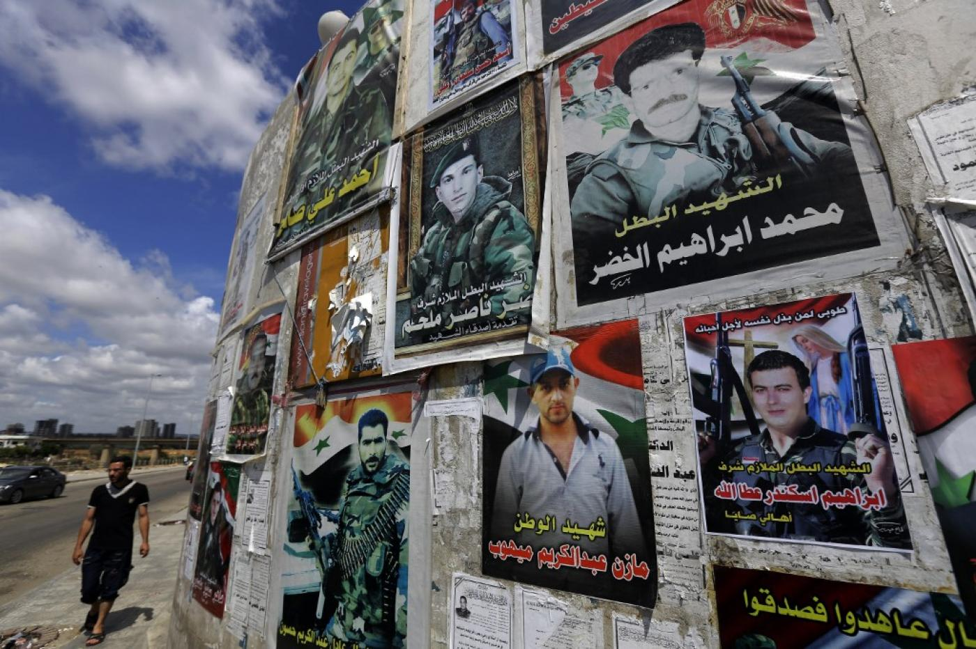 Portraits of soldiers killed fighting for the Syrian government on a wall in Tartus in 2014. Sarkha highlighted the high level of casualties among Alawite men from the city (AFP)