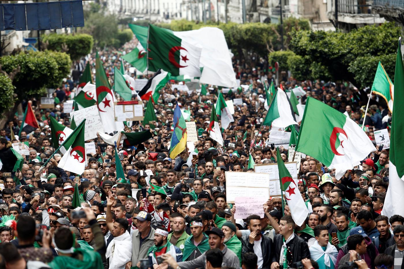 Protesters hold flags and banners in Algiers as they press demands for democratic change, April 19, 2019.