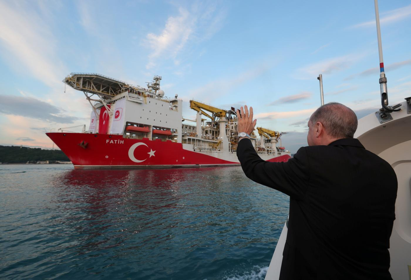 Turkish President Recep Tayyip Erdogan waves as Turkey's drilling vessel Fatih departs for the Black Sea during a ceremony in Istanbul