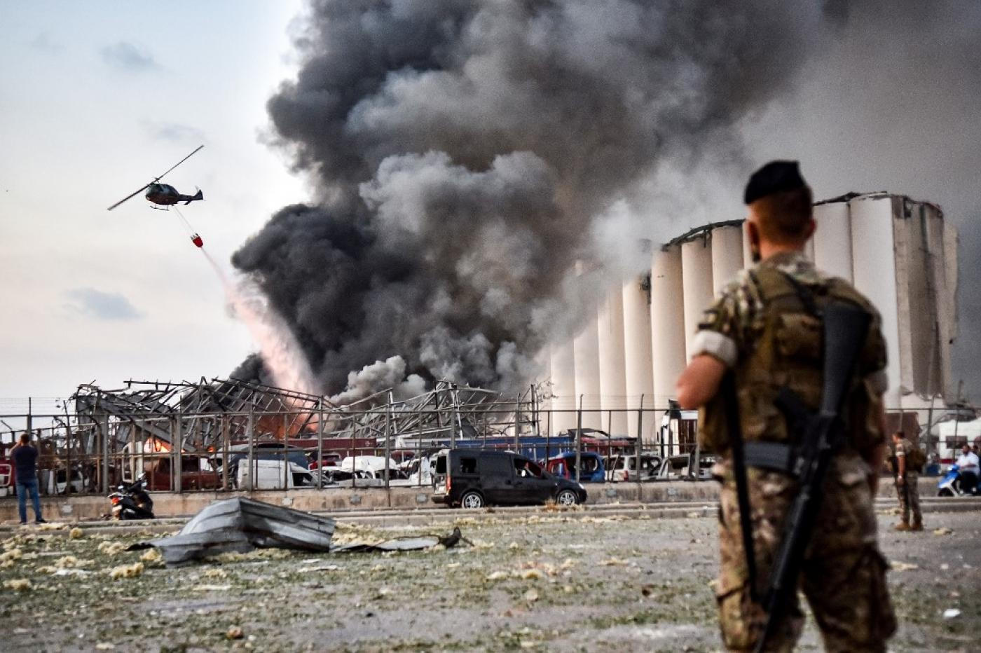 Lebanese soldiers stand guard while a helicopter puts out a fire at the scene of the explosion