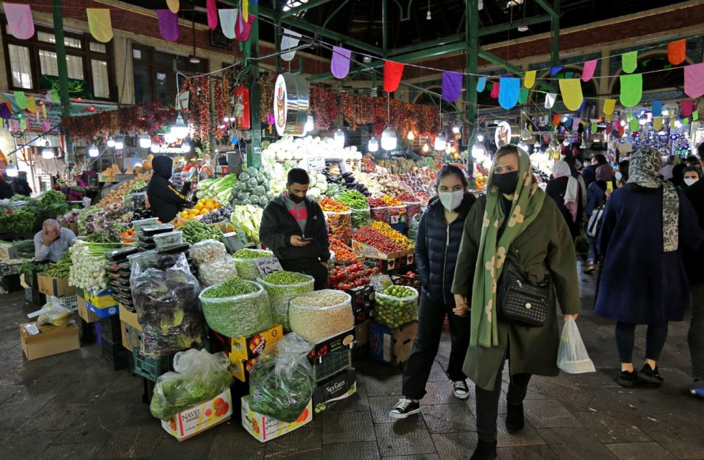 Mask-clad Iranians shop amid the Covid-19 pandemic, at the Tajrish Bazaar in Tehran on 17 March