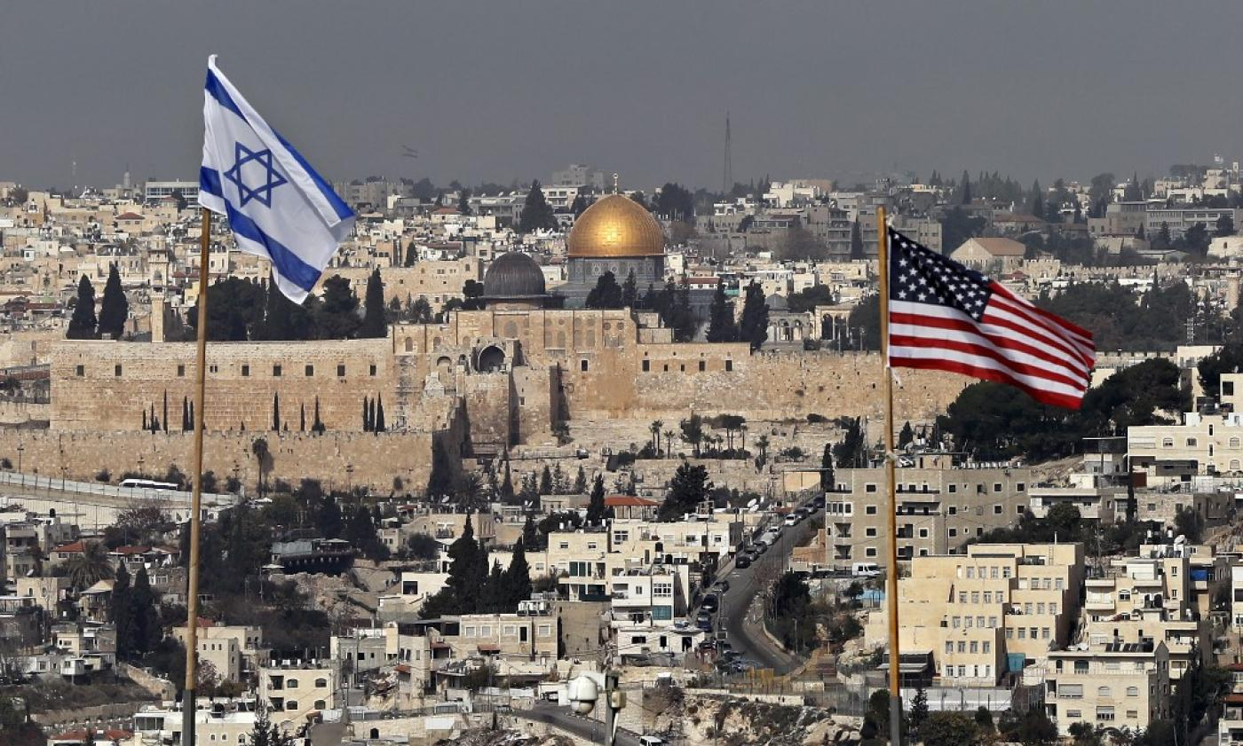 Israeli and US flags placed on the roof of an Israeli settlement building in occupied East Jerusalem