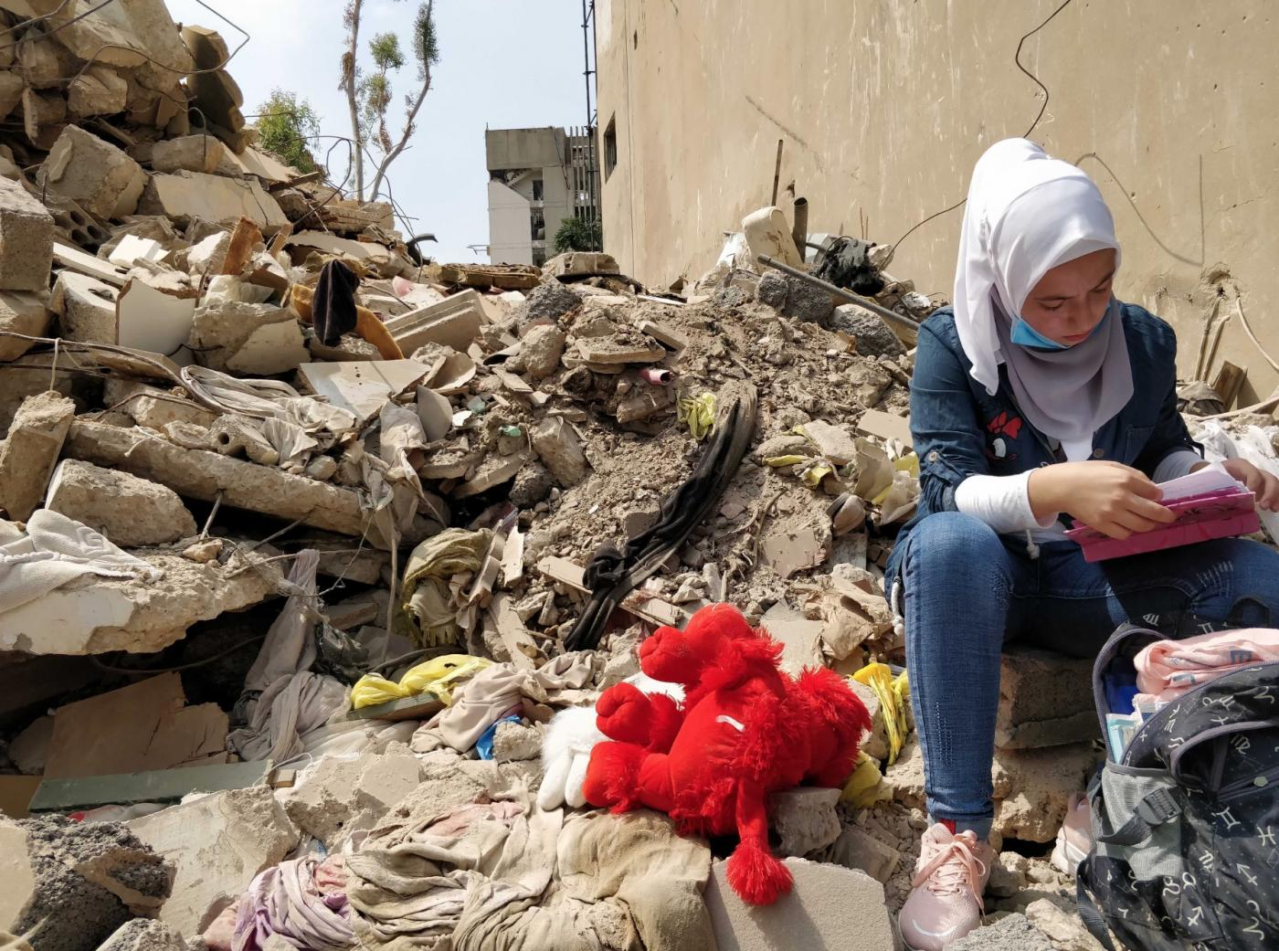 Dima, a Syrian refugee, visits her collapsed home, recovering her backpack and a teddy she found in the rubble after the explosion (MEE/Nadda Osman)