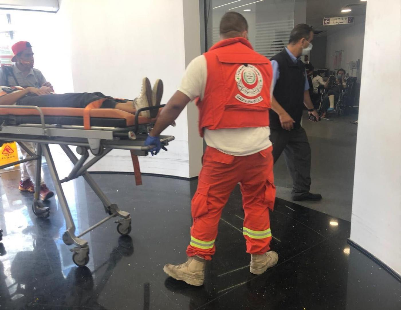 A patient carried on a stretcher at Hotel Dieu de France in Lebanon's Ashrafieh district