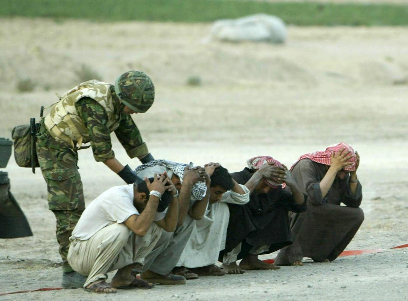 A British soldier searches Iraqis at a checkpoint on the road to Basra in 2003
