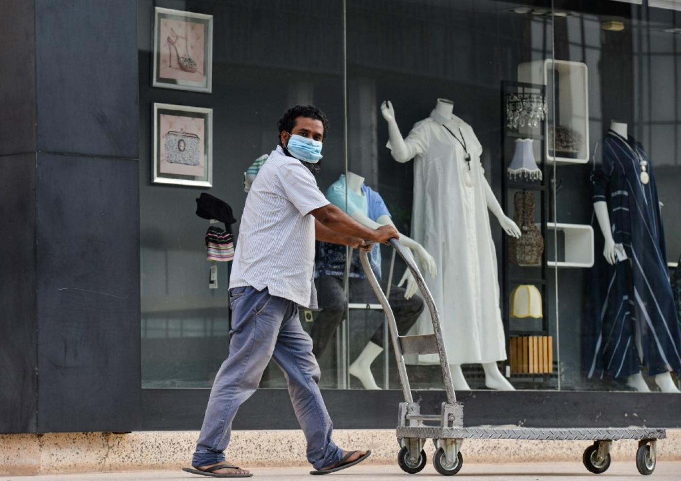 A Saudi worker wearing a mask passes a boutique shop. Riyadh reported more than 200,000 novel coronavirus cases.