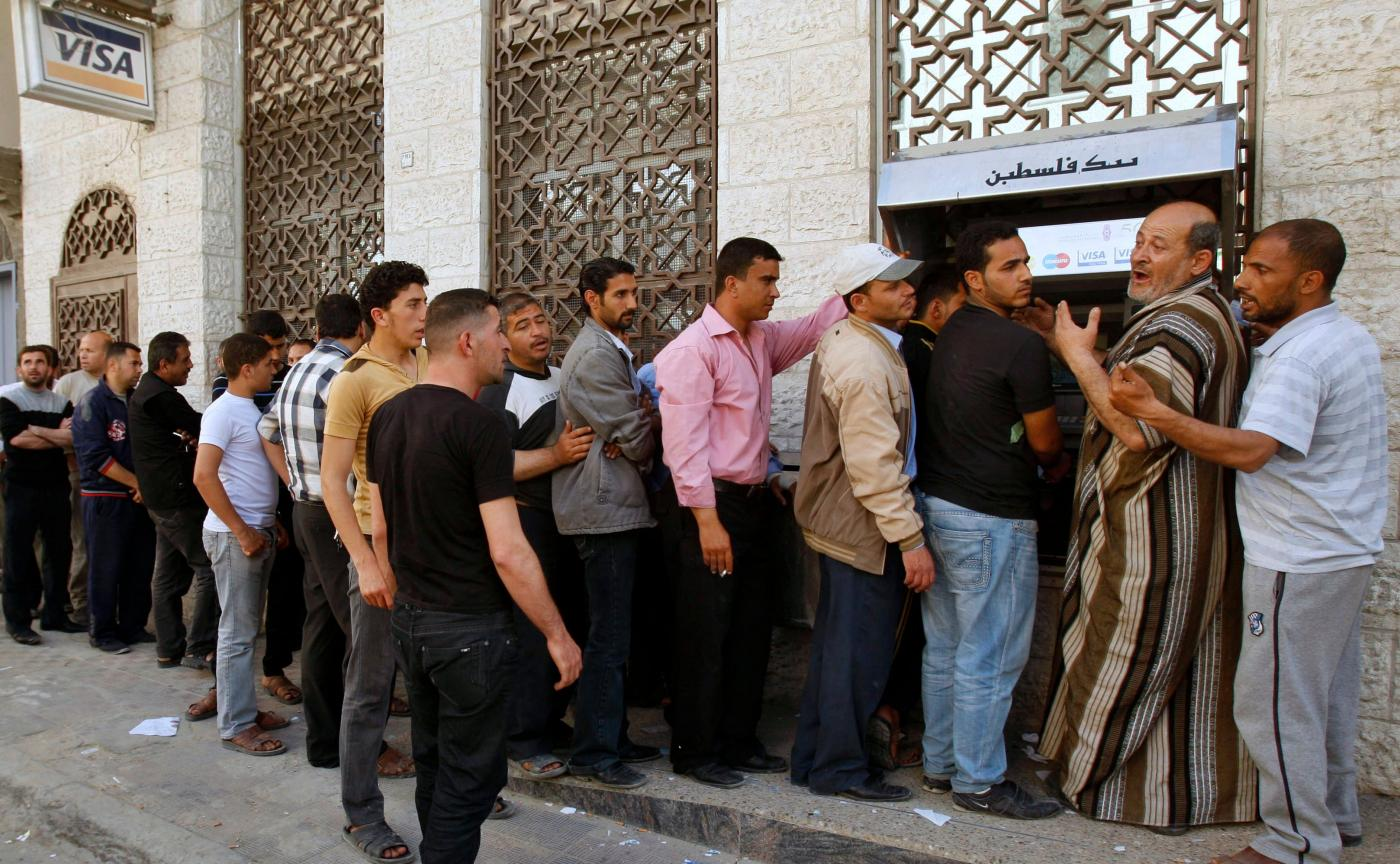 Palestinian Authority (PA) employees queue to receive their salaries from an ATM in Khan Younis in the southern Gaza Strip in April 2012 (Reuters)
