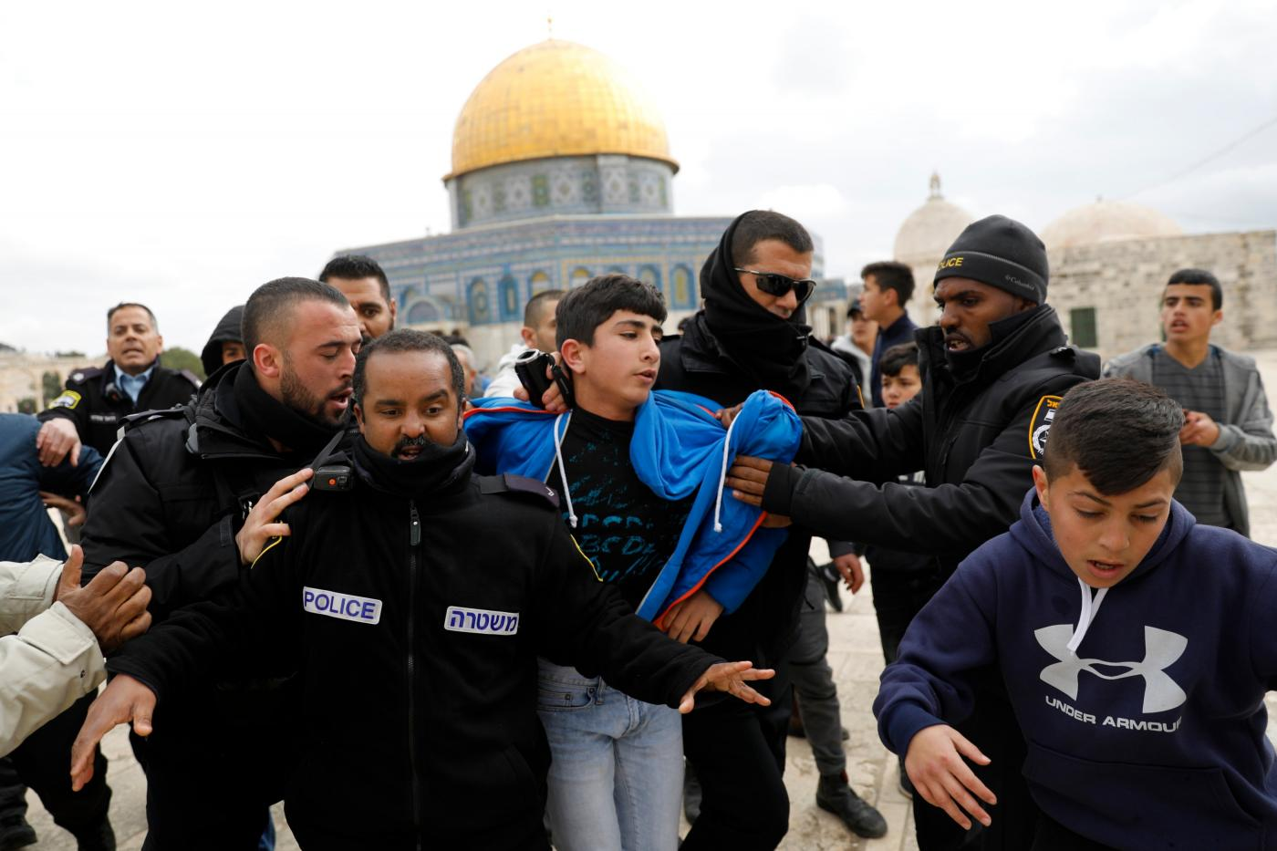 Israeli policemen detain a young Palestinian demonstrator after protesters tried to break the lock on a gate at the al-Aqsa mosque compound in Jerusalem's Old City on 18 February 2019 (AFP)