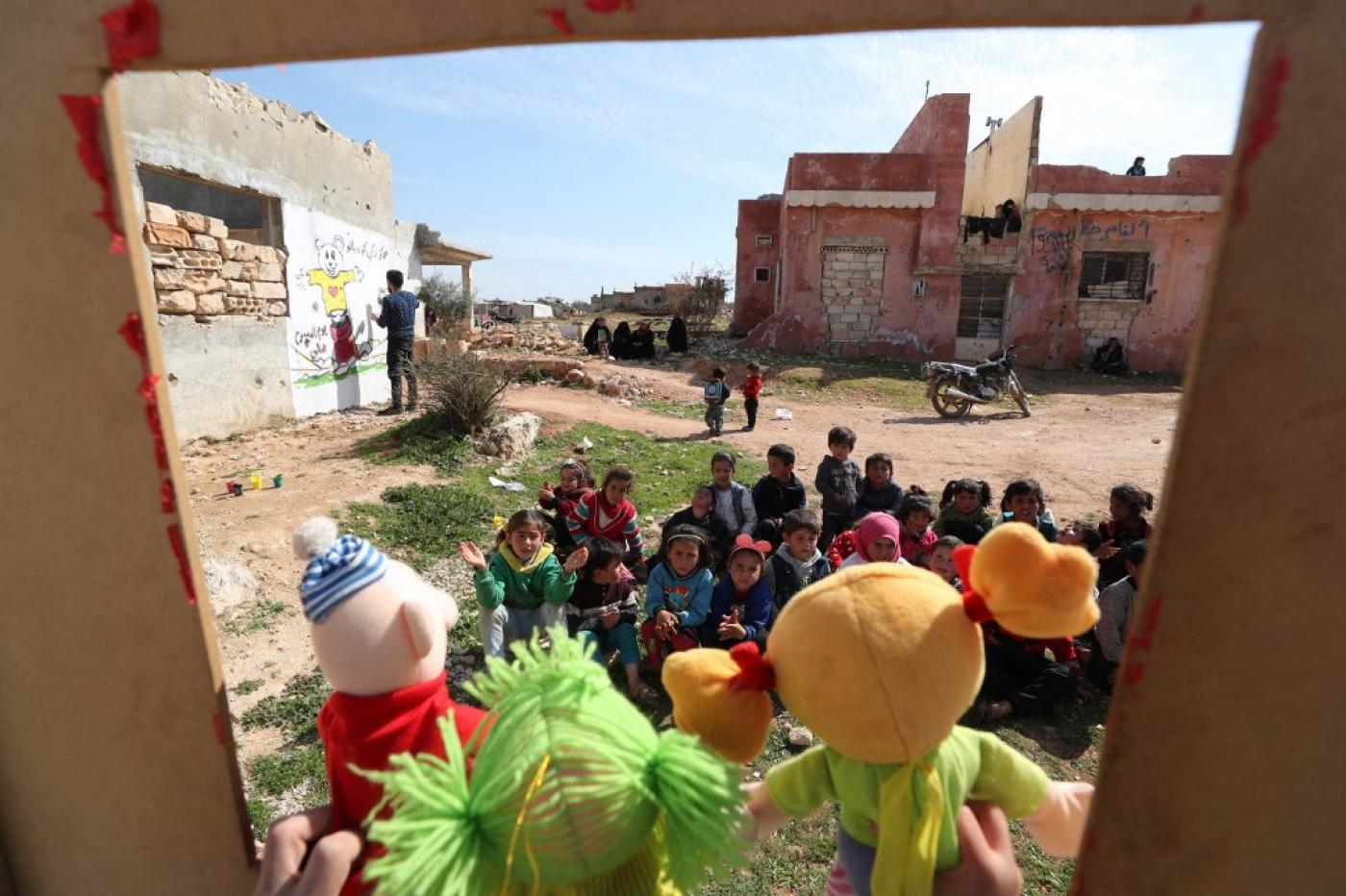 Syrian children watch a puppet show amid the ruins of buildings destroyed during Syria's civil war in the northwestern Idlib province on 30 March 2021.