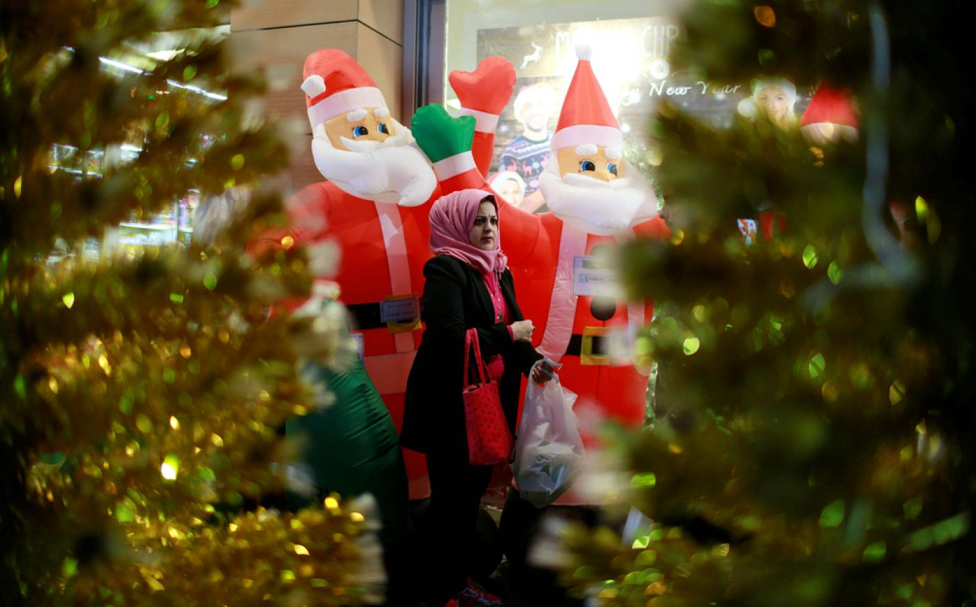 A woman walks past a store selling Christmas decorations in Baghdad, Iraq (Reuters)