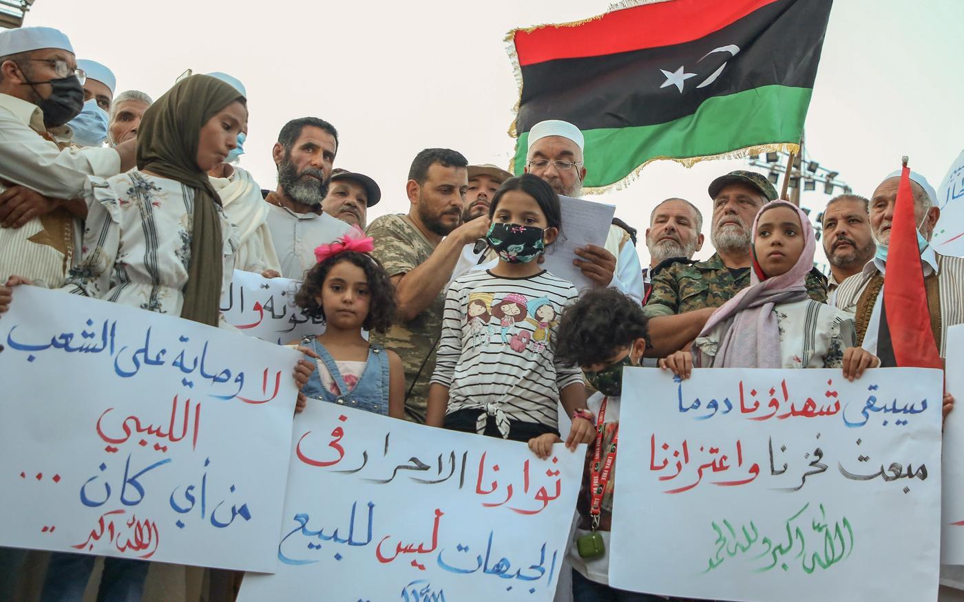 Des manifestants libyens brandissent des pancartes et des drapeaux libyens lors d'un rassemblement sur la place des Martyrs de Tripoli pour protester contre la détérioration de la situation politique et sécuritaire et des conditions de vie, le 2octobre (AFP)