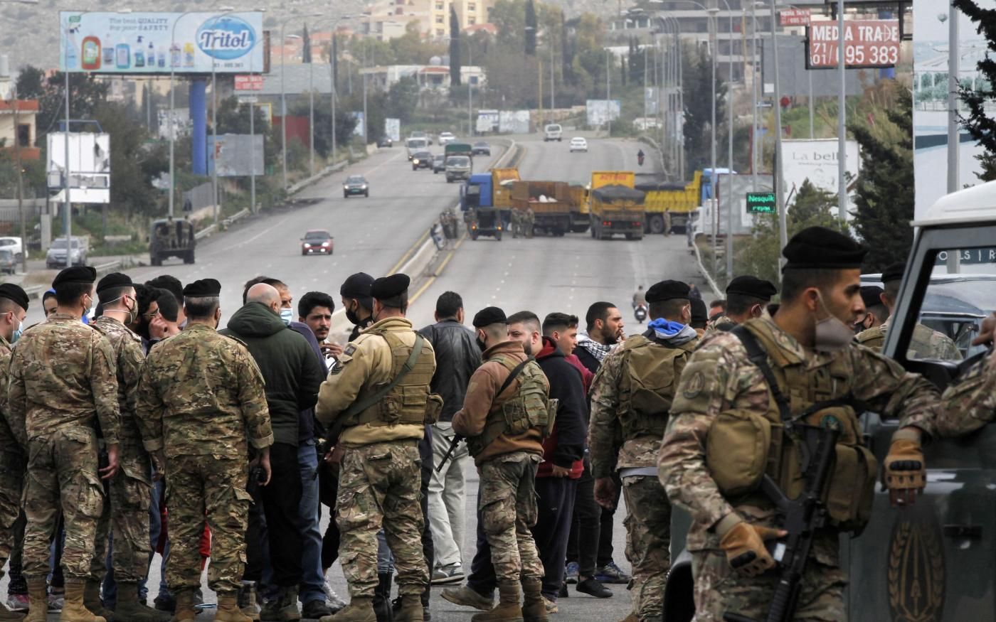 Lebanese security forces try to open a road blocked protesters south of Beirut on 10 March 2021 (Mahmoud Zayyat/AFP)