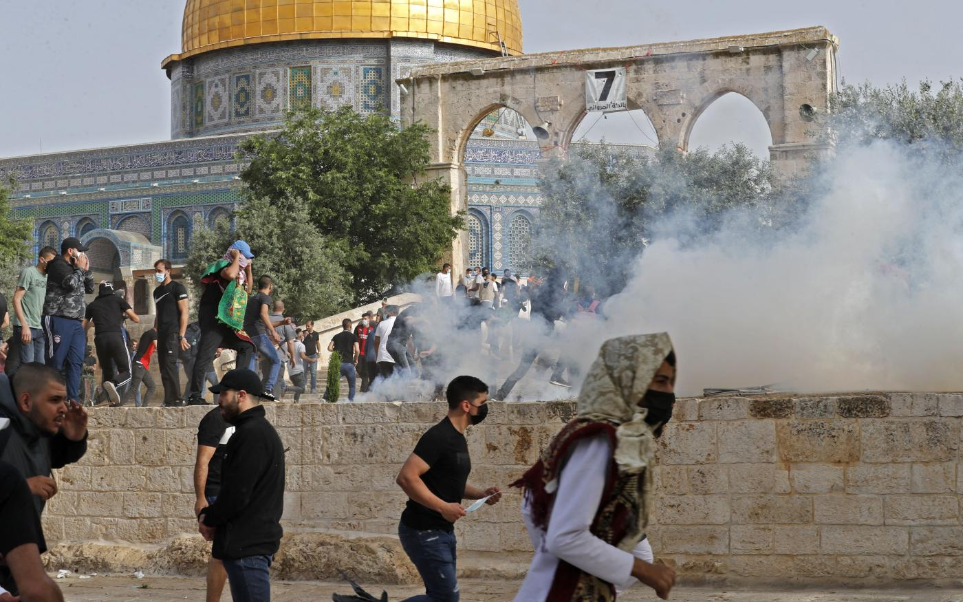 Des Palestiniens courent se mettre à l'abri après des tirs de gaz lacrymogènes dans le complexe de la mosquée al-Aqsa par la police israélienne, le 10mai2021 (AFP/Ahmed Gharabli)