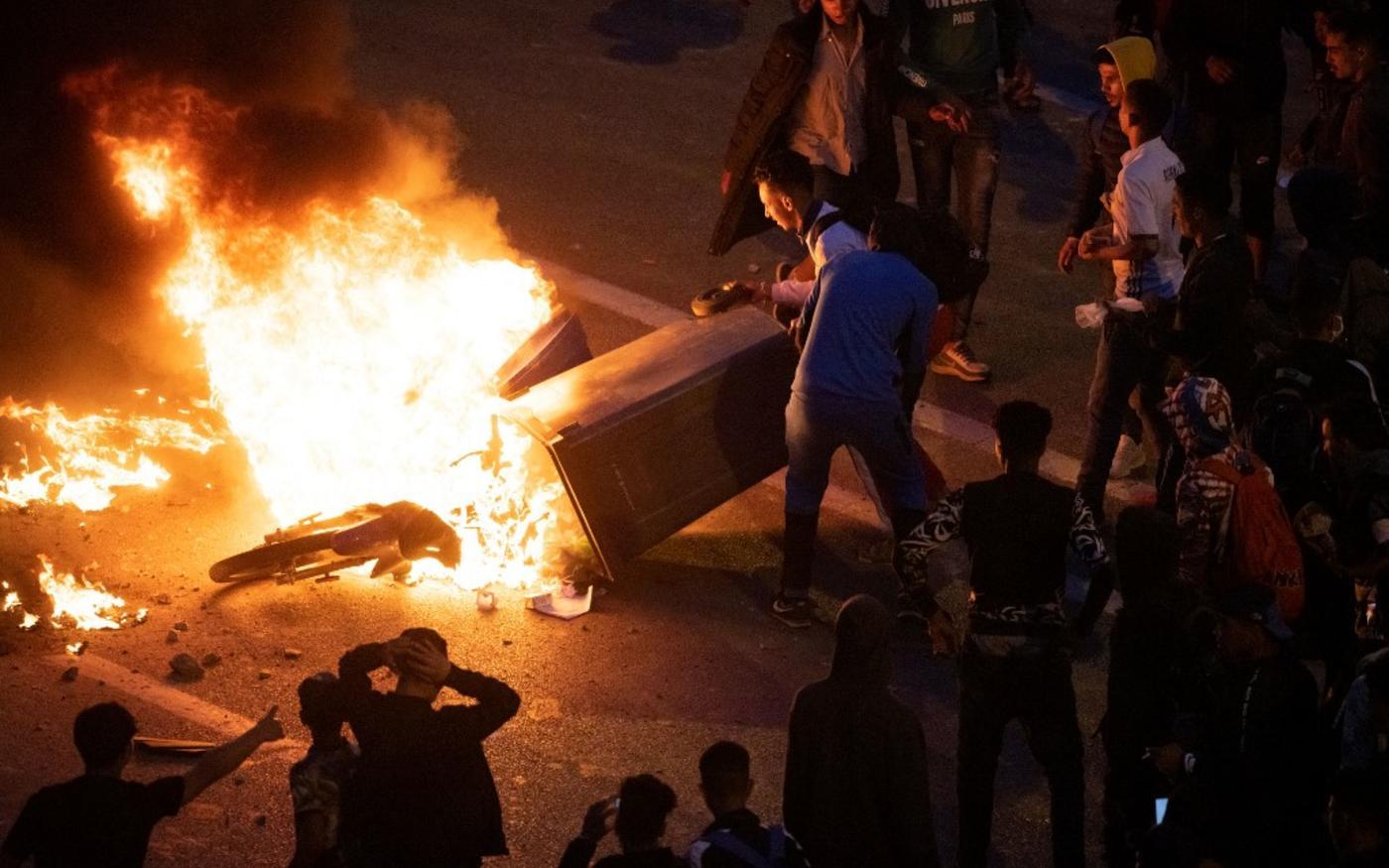 Des jeunes incendient une moto et une poubelle lors d'affrontements avec la police marocaine pour protester contre l'interdiction de franchir la frontière, à Fnideq, le 19 mai 2021 (Fadel Senna/AFP)