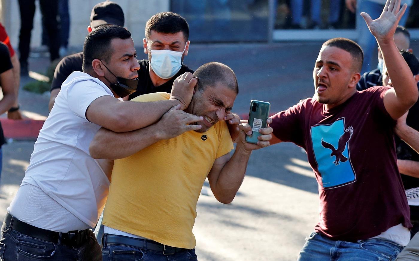 Des officiers de sécurité palestiniens en civil arrêtent un homme lors d'une manifestation à Ramallah, en Cisjordanie occupée, le 26juin2021 (AFP)