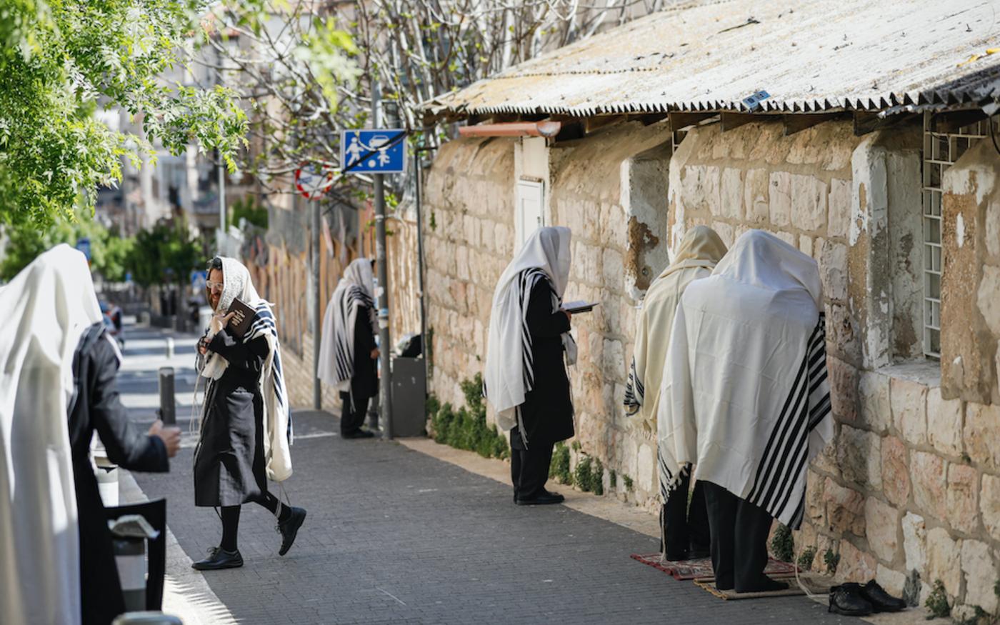 Des juifs ultra-orthodoxes prient dans une rue, à Jérusalem, le 29 mars 2020 (AFP)