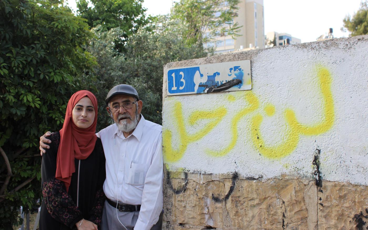 Muna et son père Nabil se tiennentcontre un mur sur lequel «Nous ne partirons pas» est tagué en arabe (MEE/Aseel al-Jundi)