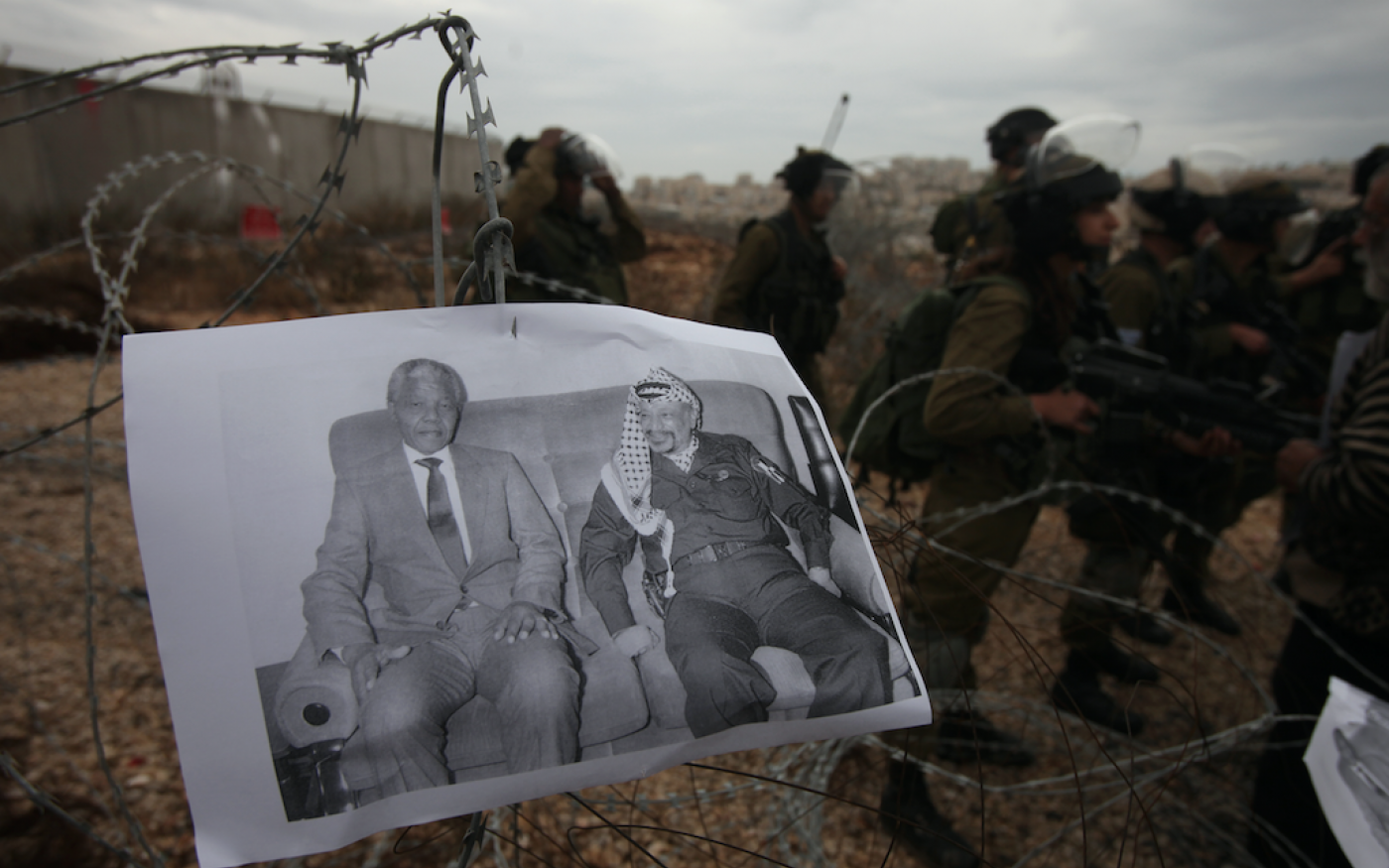 Manifestation d'activistes palestiniens contre l'occupation israélienne, dans le village de Bilin en Cisjordanie occupée, le 6 décembre 2013. Sur la photo, les dirigeants sud-africain Nelson Mandela et palestinien (Yasser Arafat) (AFP)