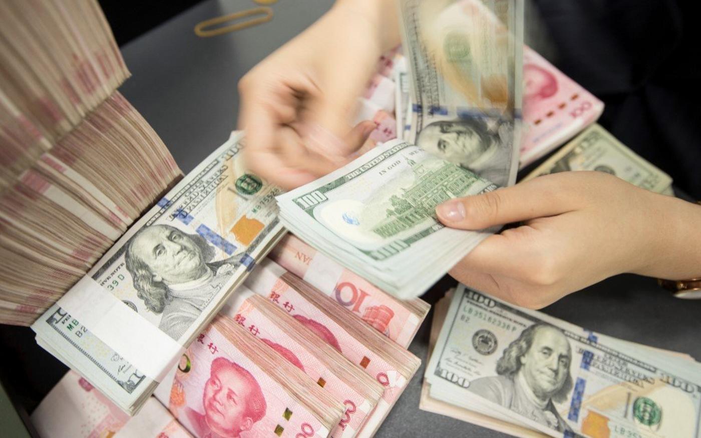Une employée de banque chinoise compte des billets en yuans et dollars américains dans le Jiangsu en 2019 (AFP)