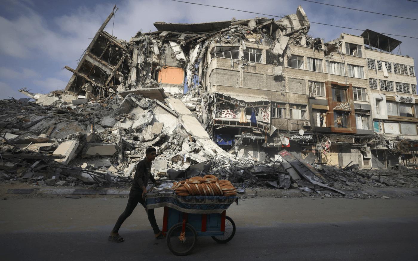 Un Palestinien passe à côté du bâtiment Al-Shuruq détruit à Gaza, le 20mai2021 (AFP/Mahmud Hams)
