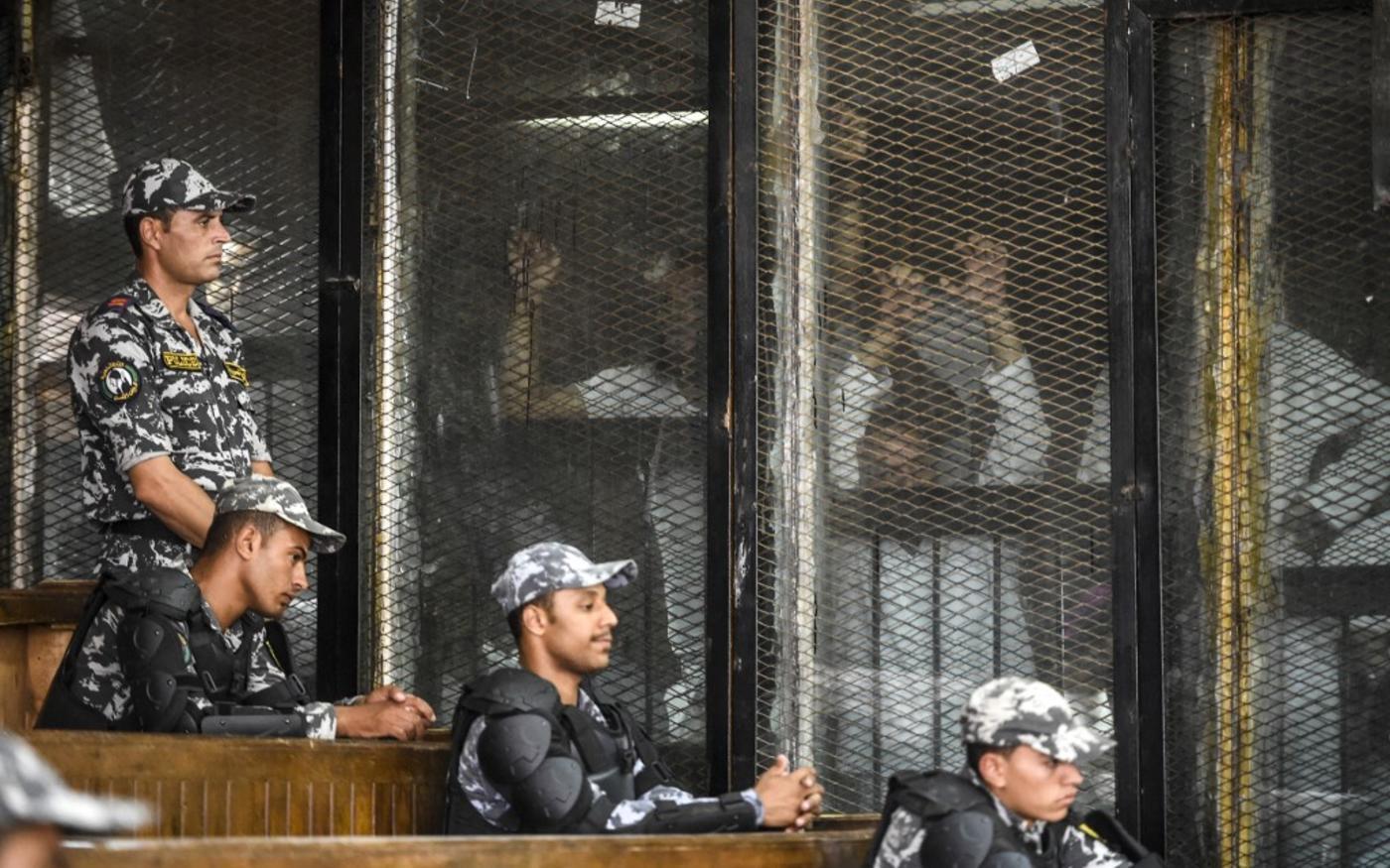 Des membres des Frères musulmans d'Égypte sont aperçus derrière des grillages et des vitres lors de leur procès en2018 au Caire (AFP)