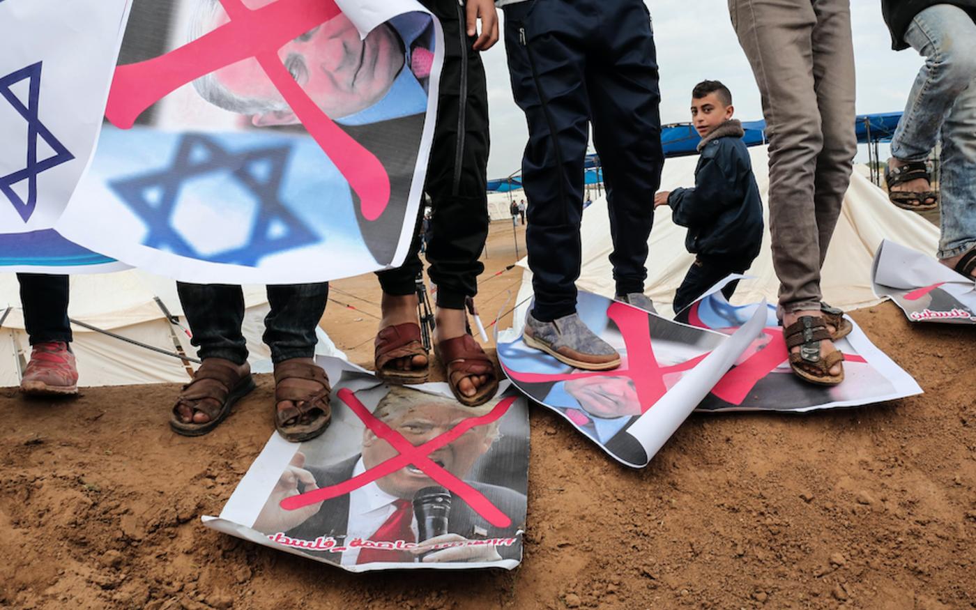 Des Palestiniens marchent sur des affiches représentant le premier ministre israélien Benjamin Netanyahu et le président américain Donald Trump, lors d'une manifestation, à Gaza, le 30 mars 2018 (AFP)