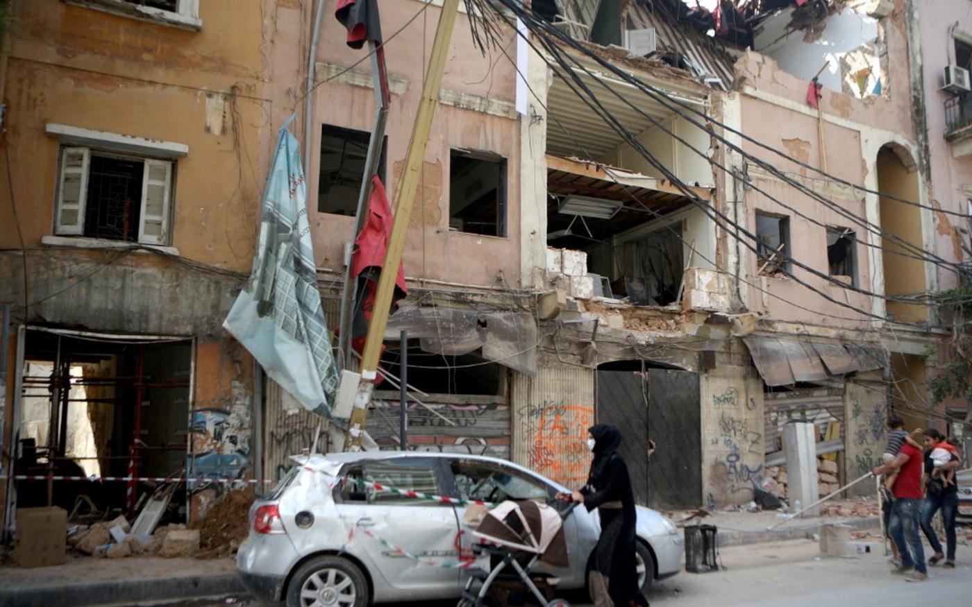Des réfugiés syriens passent devant des bâtiments endommagés dans le quartier partiellement détruit de Mar Mikhael, à Beyrouth, le 13août2020 (AFP)