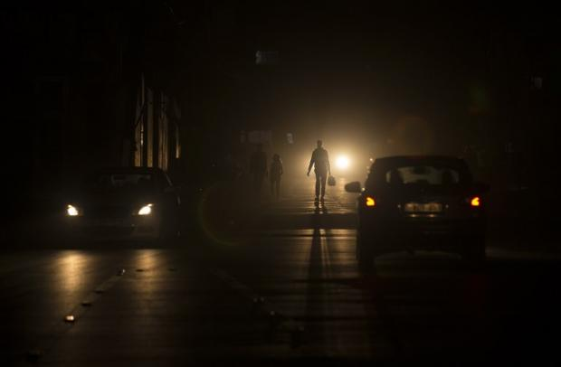 Palestinians walk on a street at the Al-Shati refugee camp in Gaza City during a power outage on 11 June (AFP)