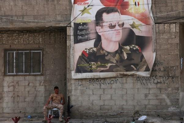 A Syrian soldier sits next to a poster of the Syrian president at the entrance of the Wafideen Camp on 12 April 2018