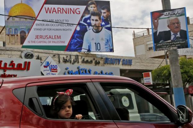 A poster in the West Bank town of Hebron highlights the Israeli occupation, while calling for a boycott of a football match with Israel, on 5 June (AFP)