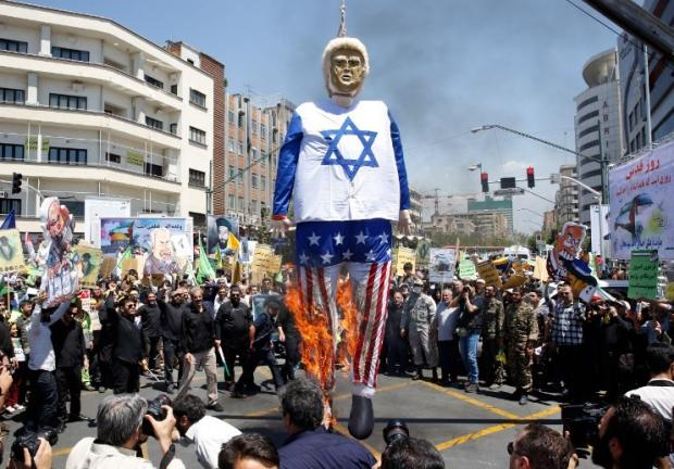 Iranian protesters burn an effigy of US President Donald Trump dressed in an Israeli flag during a rally to mark Quds Day (the day of Jerusalem) on 8 June 2018 (AFP)