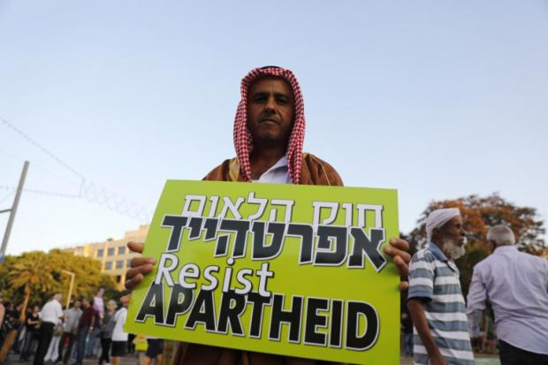 A Palestinian citizen of Israel carries a banner to protest against Israeli apartheid in Tel Aviv on 11 August (AFP)