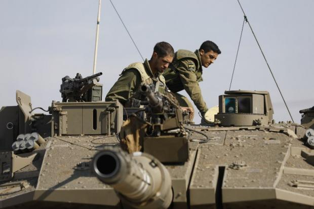 Israeli soldiers sit atop a tank stationed at the Gaza fence on 13 November (AFP)