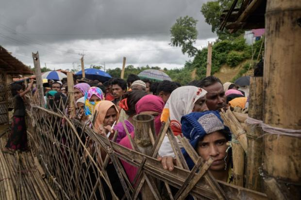 Rohingya refugees queue at an aid relief distribution centre near Cox's Bazar, Bangladesh, on 12 August 2018 (AFP)