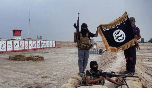 An image made available on 11 June 2014 shows IS fighters posing with their flag in Iraq (HO/Welayat Salahuddin/AFP)