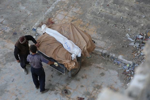Man carries dead bodies away in Aleppo (MEE/ Zuheir al-Shimale)
