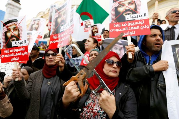 A woman takes part in a protest opposing the visit of Saudi Arabia's Crown Prince Mohammed bin Salman in Tunis