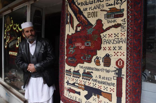 A shopkeeper in Kabul sells one of the rugs (AFP)