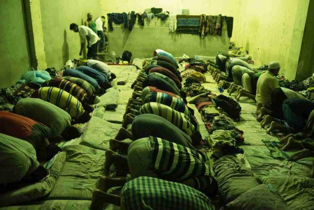 Men pray amid cramped conditions at the al Nasr centre in Zawhia (Alessio Romenzi/MEE)