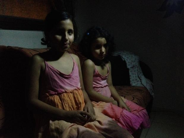 Deena and her younger sister Ala wait in the dark as bombs fall (MEE / Mohammed Omer)