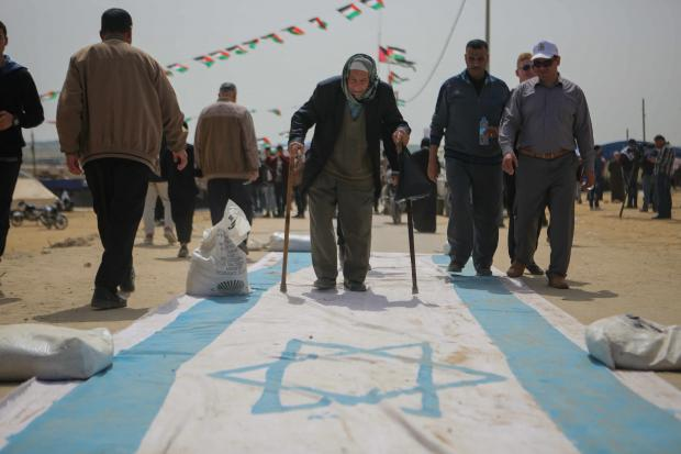 An elderly Palestinian man walks over a large Israeli flag at one of the protest camps along Gaza's borderline with Israel