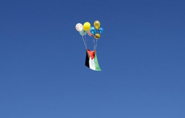 A Palestinian flag tied to ballons float away in Jerusalem