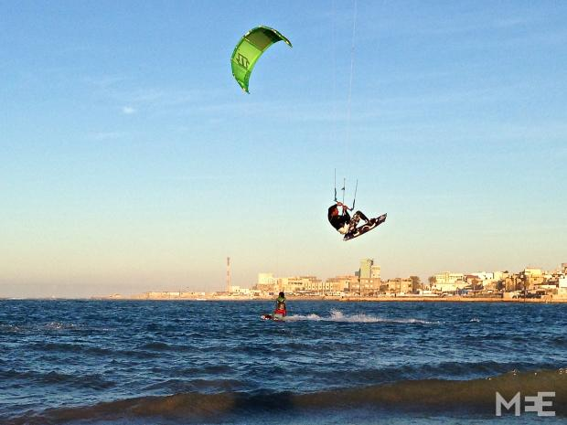 Jalal, one of the country's more experienced kiters, performing a jump with Tripoli's skyline in the background (MEE/Tom Wescott)