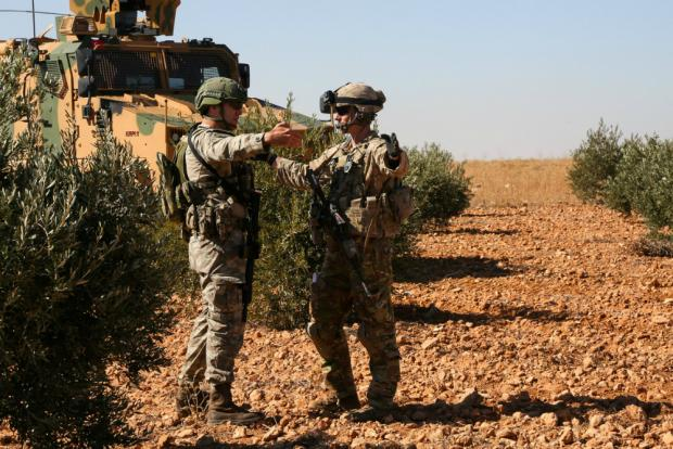 Turkish and US soldiers in discussion during a joint patrol in Manbij, Syria, in November (Reuters)