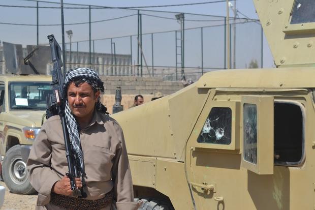 Peshmerga fighters stand next to damaged vehicles (MEE / Sheren Khalel)