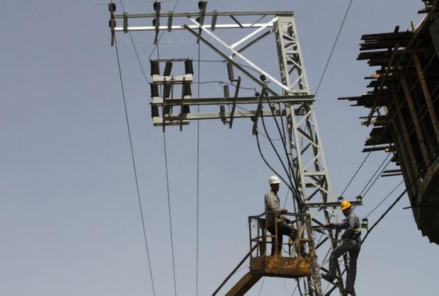 A couple of Gazan electricity company employees work to repair power lines (MEE/Mohammed Asad)